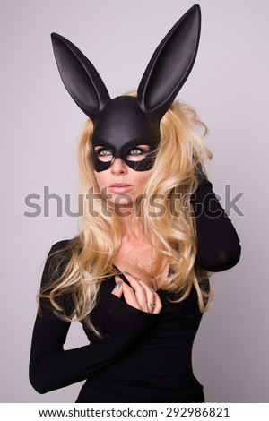 Beautiful blonde-haired young woman in carnival mask ballroom rabbit with long ears sensual sexy in a black dress, standing defiantly on a white background. - stock photo