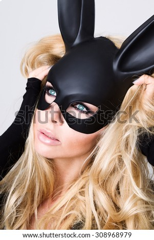 Beautiful blonde-haired young woman in carnival mask ballroom rabbit with long ears sensual sexy in a black dress, standing defiantly on a white background, finger clog the mouth for silence - stock photo