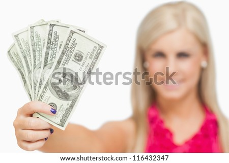 Beautiful blonde holding 100 dollars banknotes against white background