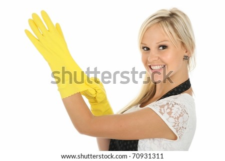Beautiful blonde housewife putting on yellow latex cleaning gloves - stock photo