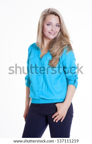 Beautiful blonde in a blue blouse and pants rehearsing a photo shoot