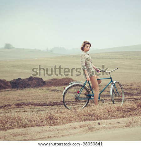 beautiful blonde in a dress on a bicycle - stock photo