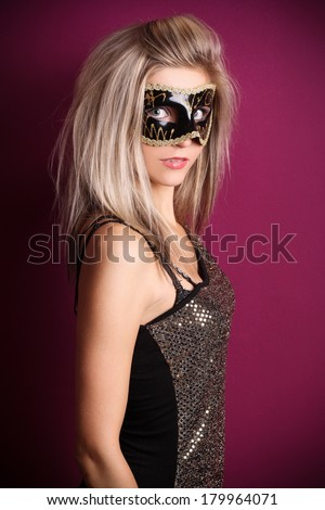 Beautiful blonde in a dress with a eye mask posing on a purple background, in the studio, fashion photography - stock photo