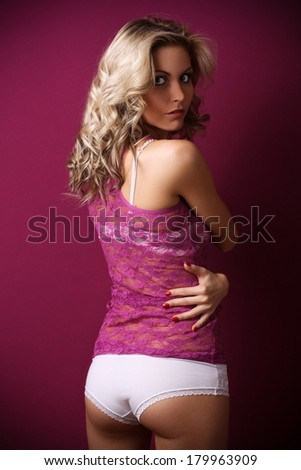 Beautiful blonde in a transparent purple shirt and white underwear posing on a purple background, in the studio, fashion and glamour photography - stock photo