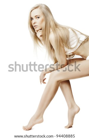 Beautiful blonde in a white peignoir. Sits, looks to camera - stock photo