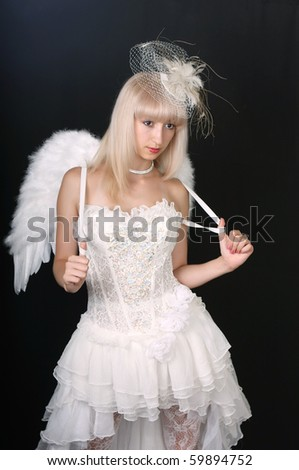 beautiful blonde in an extravagant hat and white dress with wings - stock photo
