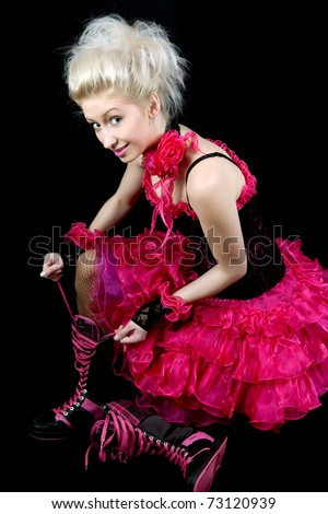 beautiful blonde in black and pink dress shoes tying shoelaces - stock photo