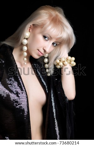 beautiful blonde in shiny black cape and pearl jewelry - stock photo