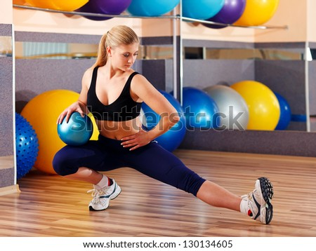 Beautiful blonde in sport gym with sports balls - stock photo