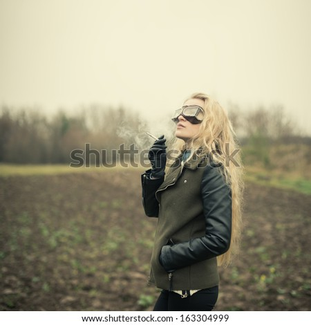 beautiful blonde in the form of a pilot smoking resting - stock photo