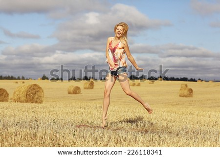 beautiful blonde jumps in sloping field sun happiness - stock photo