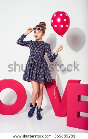 Beautiful blonde kid girl posing with a balloon  isolated on white. Children fashion photo - stock photo