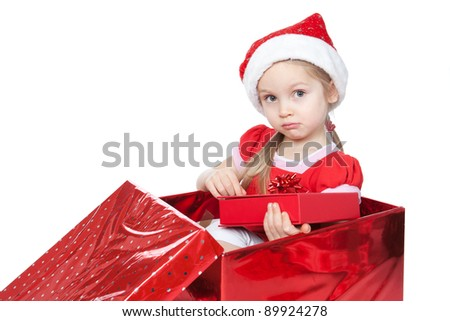 Beautiful blonde little girl dressing in Santa's Helper hat sitting in a Christmas present box over white - stock photo