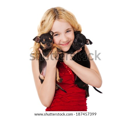 beautiful blonde little girl holding two puppies wearing red dress - stock photo