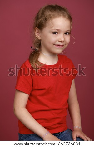Beautiful blonde little girl, isolated on plum background