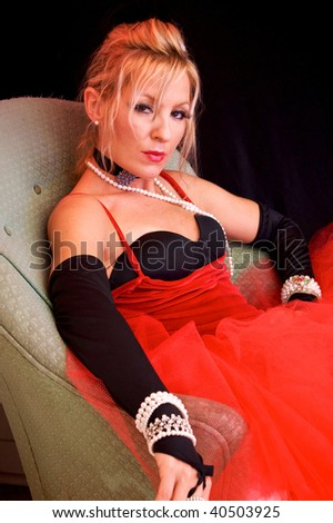 Beautiful blonde looking at viewer seductively. Actress dressed up as a sexy mrs. claus or santa's elf for christmas or an old fashioned madam or prostitute. Shot with blue and red colored strobes. - stock photo