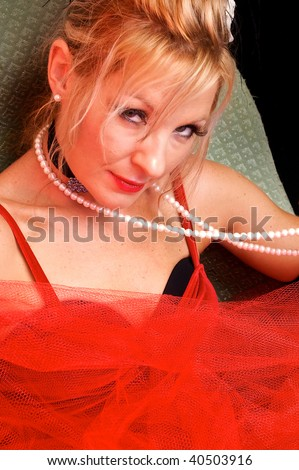 Beautiful blonde looking at viewer smiling. Actress dressed up as old fashioned madam or prostitute can also be a sexy mrs. claus or santa's elf for christmas. Shot with blue and red colored strobes. - stock photo