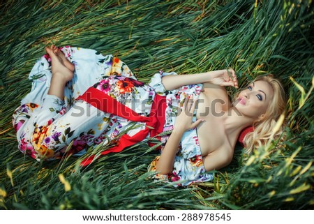 Beautiful blonde lying on the grass crumpled. She has dreamy eyes. She looks sexy. - stock photo