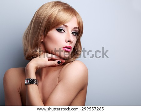 Beautiful blonde makeup female model posing in fashion watches on the hand on blue background with empty copy space - stock photo