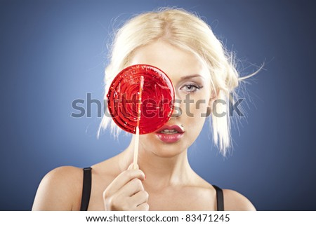 Beautiful blonde model hides her face behind a big round red lollipop. - stock photo