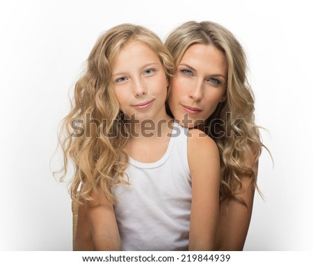 Beautiful blonde mother and her daughter together, family portrait