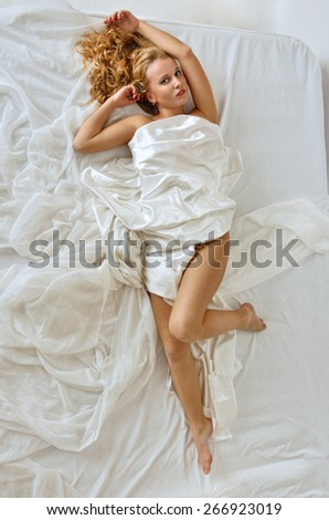 Beautiful blonde naked woman laying on white bed. View from above.