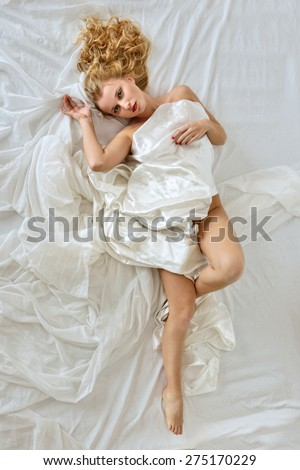 Beautiful blonde naked woman laying on white bed. View from above. - stock photo