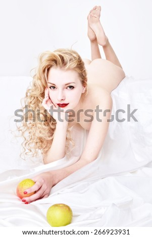 Beautiful blonde naked woman with apple lying on the white bed. Eva shape. - stock photo