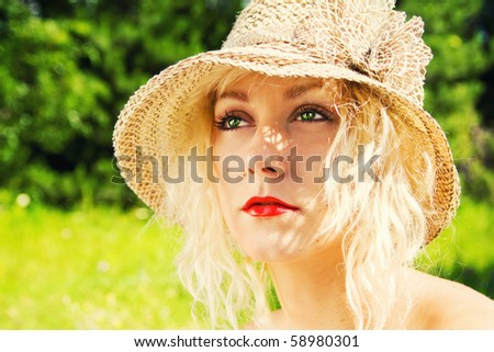 Beautiful blonde on a meadow wearing a hat - stock photo