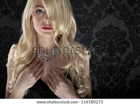 Beautiful blonde on dark textile wallpaper background - stock photo