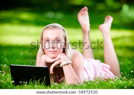 Beautiful blonde on the green grass with laptop - stock photo