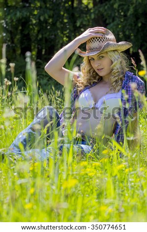 Beautiful blonde relaxing in the forest meadows. - stock photo