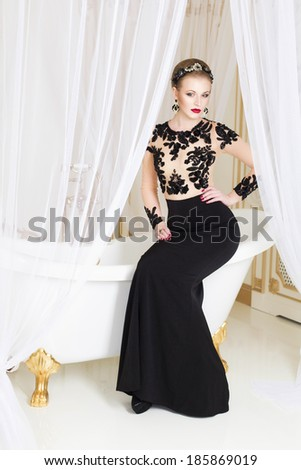 Beautiful blonde royal woman sitting on a bathtub with tulle on it in gorgeous luxury dress. Indoor - stock photo