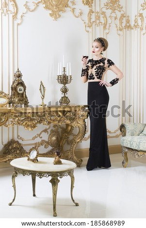 Beautiful blonde royal woman standing near retro table in gorgeous luxury dress with glass of wine in her hand. Indoor. Copy Space - stock photo