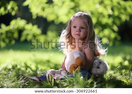 Beautiful blonde sad little girl in a park - stock photo