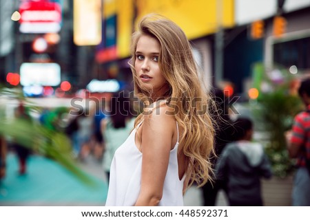 Beautiful blonde sexy tourist girl walking in busy city street with long hair flying on the wind. Woman looking at camera outdoors wearing fashionable white t-shirt. New York City lifestyle photo. - stock photo