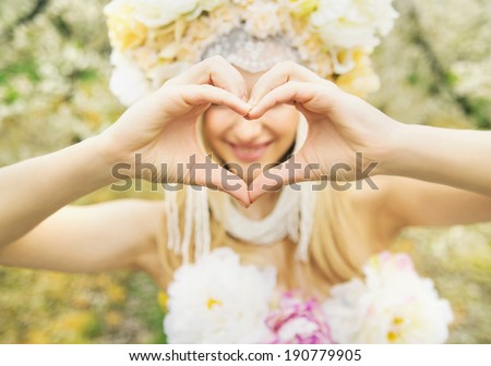 Beautiful blonde showing heart shape - stock photo