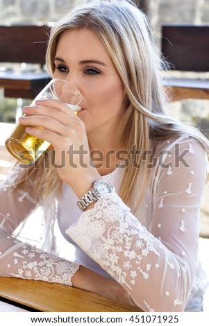 Beautiful Blonde sipping a glass of beer/cider - stock photo