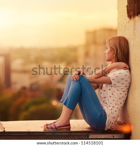 beautiful blonde sitting on the roof of the house - stock photo