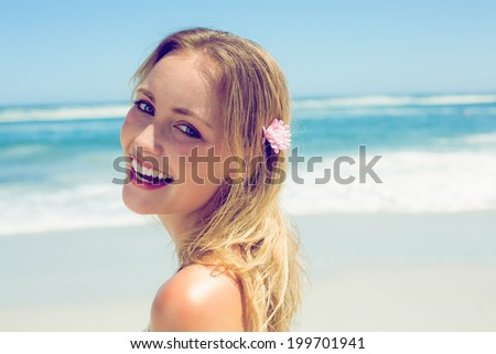 Beautiful blonde smiling at camera on the beach on a sunny day - stock photo