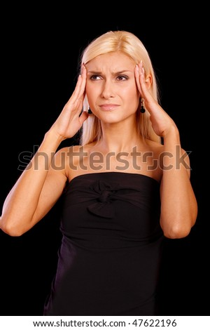 Beautiful blonde suffers headache, it is isolated on black background. - stock photo