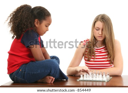 Beautiful blonde teen and adorable preteen playing a game of chess. - stock photo