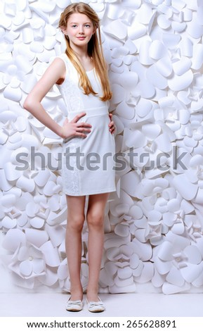 Beautiful blonde teen girl wearing white dress posing by a background of white paper flowers. Beauty, fashion. Full length portrait. - stock photo