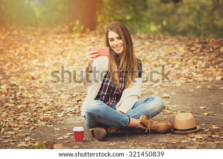 Beautiful blonde teenage girl wearing casual modern autumn outfit sitting in park in autumn taking a selfie on smartphone. Horizontal, retouched, vibrant colors, brownish tones. - stock photo