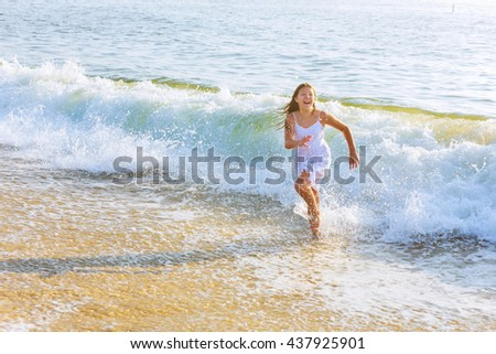 beautiful blonde teenage girl wearing flowy white dress standing ankle dee in ocean water - stock photo