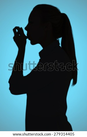 Beautiful blonde using an asthma inhaler against blue background with vignette - stock photo