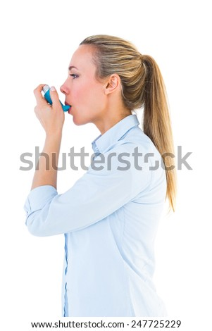 Beautiful blonde using an asthma inhaler on white bakcground - stock photo