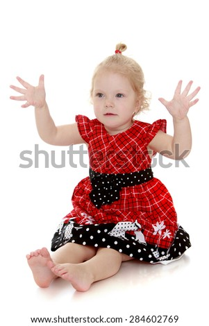 Beautiful blonde very little girl led on the floor with bare feet with his two hands to the side- isolated on white background - stock photo
