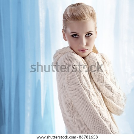 beautiful blonde with an up-do wearing a white and warm woolen sweater - stock photo