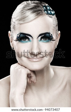 Beautiful blonde with artistic makeup over black background